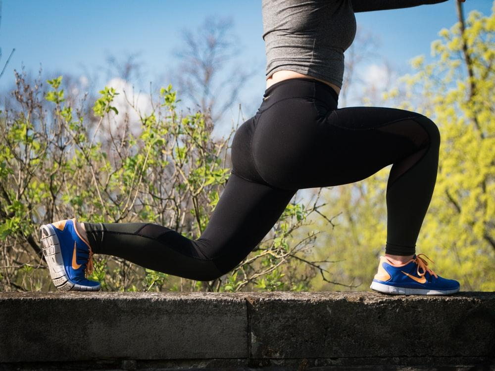 woman stretching her legs on top of the wall