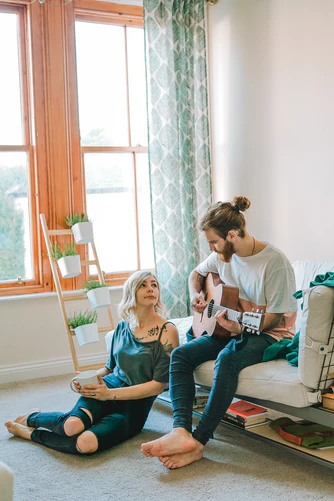 Man Sitting on Sofa Playing Guitar Looking at Girl